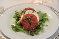 plate with tomato mozzarella on bed of greens