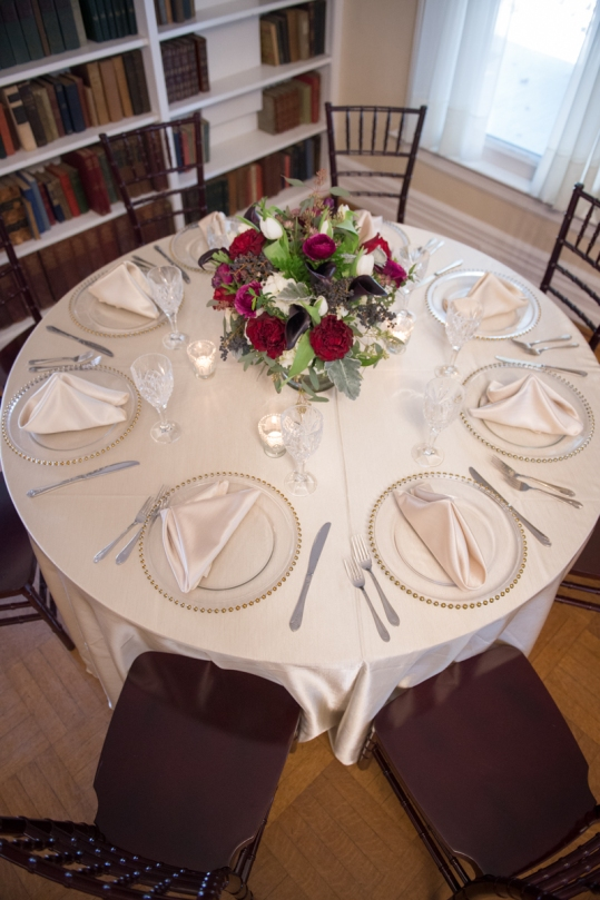 looking down on a table with silver and gold accents with red and white flowers