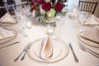 table setting with gold rimmed clear plates with silver accents
