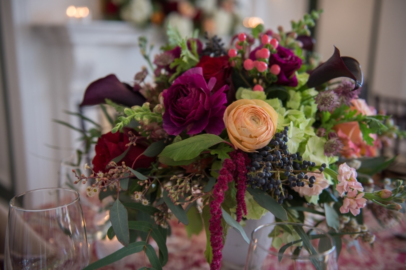 red and peach roses sprinkled with berries and greens