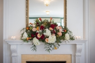 white hydrangia, red, pink roses flowing across fireplace mantle