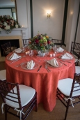 dark flower arrangement with rust linens and dark chivari chairs