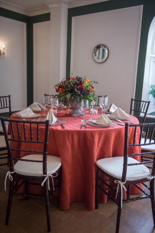 dark flower arrangement with rust linens and dark chivari chairs