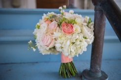 pink and coral roses with white hydrangea tied with coral ribbon