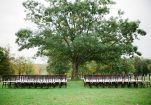 chairs set up in front of beautiful tree for ceremony