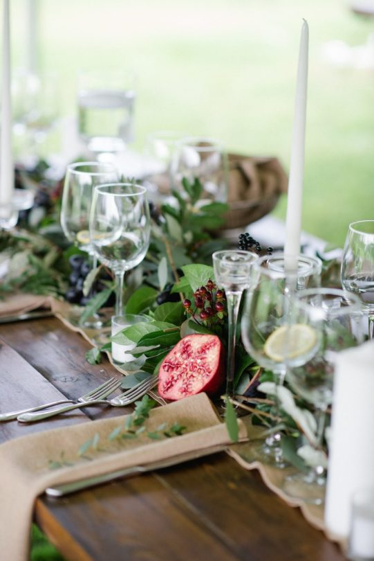 table set with wine glasses, candles and pomegranate