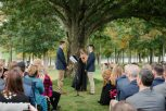 vows being exchanged in front of guests under tree