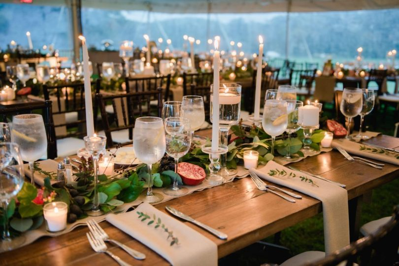 guest seating under the tent set with hundreds of candles
