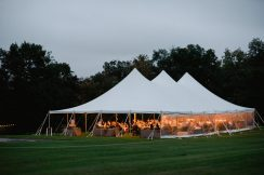 lighted tent set up on lawn with cloudy sky