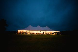 sillouette of lighted tent on lawn under dark sky